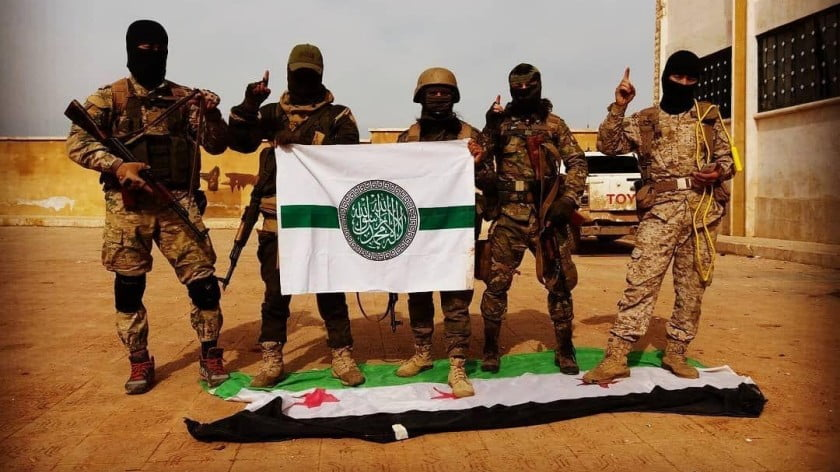 "Al-Qaeda militants standing on the ""Moderate Free Syrian Army"" flag after defeating its fighters in north Syria."