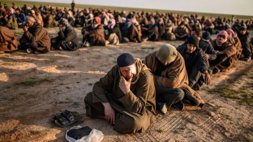 Men suspected of being Islamic State (IS) fighetrs wait to be searched by members of the Kurdish-led Syrian Democratic Forces (SDF) after leaving the IS group's last holdout of Baghouz, in Syria's northern Deir Ezzor province on February 22, 2019. (Photo by Bulent KILIC / AFP) (Photo credit should read BULENT KILIC/AFP/Getty Images)