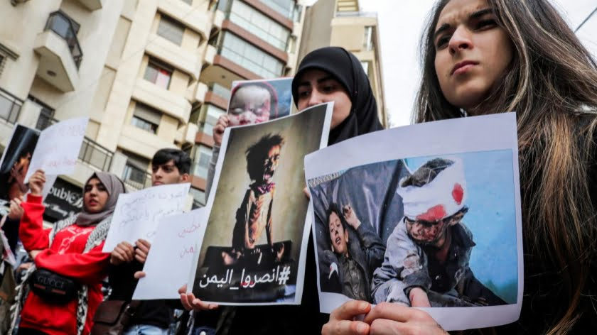Lebanese protesters hold up pictures of children affected by the war in Yemen, during a demonstration outside the Saudi embassy in the capital Beirut on 2 December, 2018 (AFP)