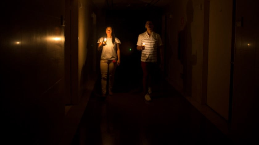 Relatives of a patient walk in the darkened hall of a clinic with a candle lighting the way, during a power outage in Caracas, Venezuela, March 7, 2019. A power outage left much of Venezuela in the dark in what appeared to be one of the largest blackouts yet. Ariana Cubillos | AP