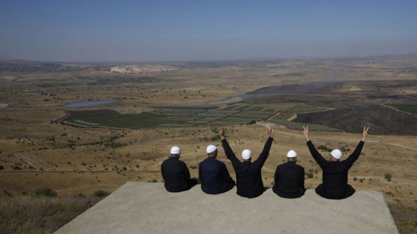 Druze men at the Israeli-annexed Golan Heights flash the V for victory sign as they look out across the southwestern Syrian province of Quneitra, visible across the border on July 7, 2018 (Photo by JALAA MAREY / AFP) (Photo credit should read JALAA MAREY/AFP/Getty Images)