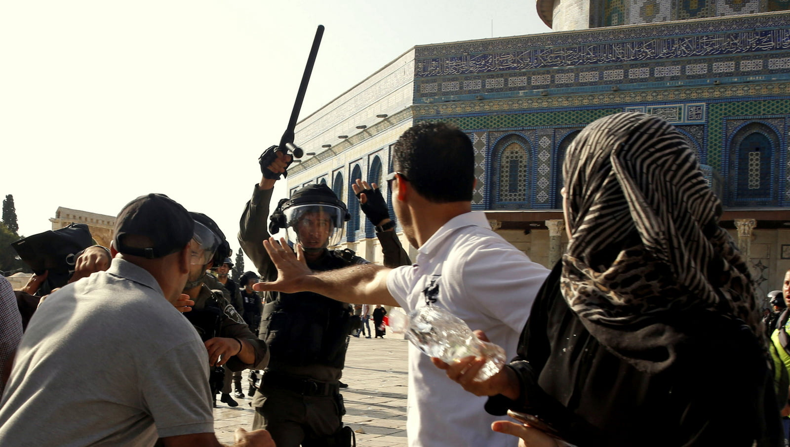 An Israeli police officer raises his baton on Palestinians worshipers near the Al Aqsa Mosque in Jerusalem's Old City, July 27, 2017. Mahmoud Illean | AP