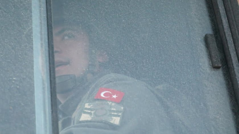 A Turkish military personnel looks out the window of a military vehicle as it enters the Bab al-Hawa crossing at the Syrian-Turkish border in Idlib on 9 February (Reuters)